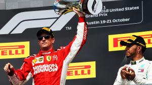 Räikkönen håller upp sin pokal, Hamilton applåderar.