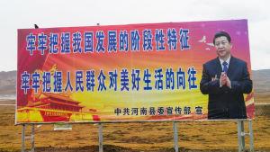 Iso juliste keskellä autiota näkymää. Julisteessa kiinankielistä tekstiä ja Xi Jinping.