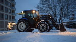 En traktor som plogar snö en tidig vintermorgon. Strålkastarna på traktorn lyser.