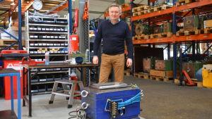 Man i blå tröja och beiga byxor står bakom en fabriksform och framför varuhyllor i en fabriksbyggnad.