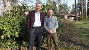 två män framför buske