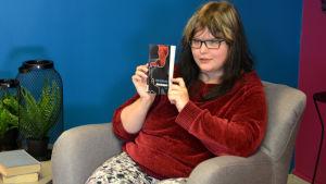 kvinna i fåtölj med bok