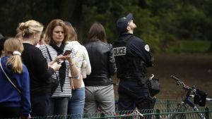 Turister och polis utanför det evakuerade Eiffeltornet.