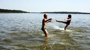 Två barn leker i vattnet under en varm sommardag.