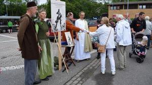 Några utklädda skådespelare från teatergruppen Fjerden delar ut information om En midsommarnattsdröm på Dalsbruks torg.