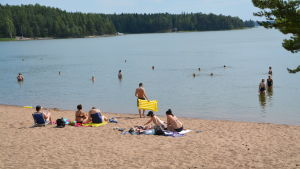 Folk simmar vid en badstrand.