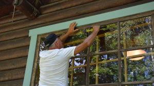 Henry Leandersson lappar ett söndrigt fönster.