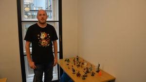 En man står framför ett bord med spelfigurer.