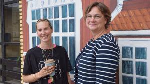 Två kvinnor står bredvid varandra och ler mot kameran. Bakom dem finns en målning och fönster.