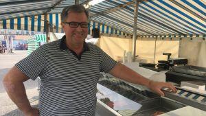 Stefan Rehn står framför fiskdisken vid sitt försäljningsstånd.