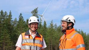 Två män med skyddsvästar och -hjälmar. I bakgrunden skymtar ett vindkraftverk.