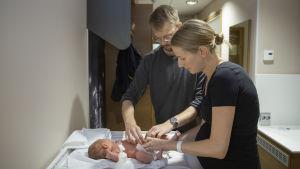 Sofia Tigerstedt och Jussi Ukkonen byter blöja på sin nyfödda dotter på patienthotellet Familjeboet i Helsingfors.