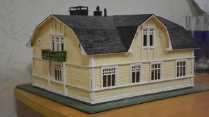 Ett miniatyrhus gjort av tändstickor. Målat i gulvitt med svart tak.. Miniatyr av Klubbhus Fontana i Karis