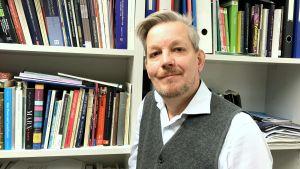 en man i vit skjorta och grå väst står framför en massa böcker i bokhyllor