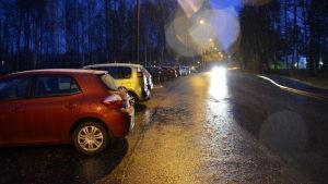 Bilar parkerade längs väg i regnväder.