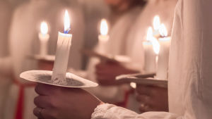 Luciatåg som håller ljus i sina händer
