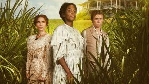 Kaksi naista ja mies seisovat viljelmällä takanaan talo.
