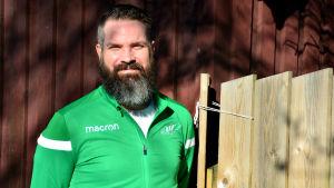 man i grön träningsjacka invid staket