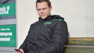 Zacharias Ekström sitter med telefonen i handen.