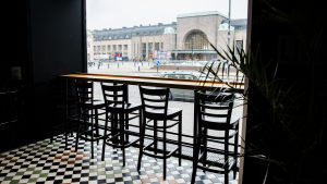 Fyra tomma restaurangstolar framför ett fönster intill Helsingfors järnvägsstation.