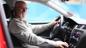 Peter wendell sitter i bilen med ena handen på ratten och andra på växelspaken