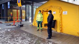 Mikkelin keskussairaalan päivystyksen ulko-ovella sairaalan työntekijöitä sekä koronateltta.