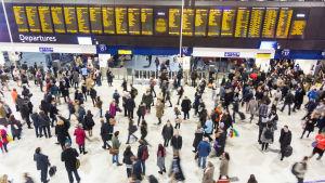 Terminal med massor människor som går omkring under massiv tavla med avgående tåg.