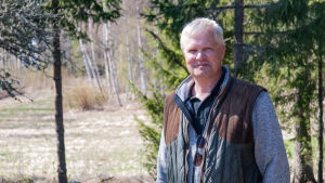 En man står i ett skogsbryn