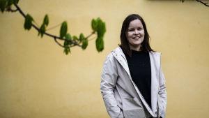 Professorn i EU-rätt Päivi Leino-Sandberg står framför en gul vägg och ler mot kameran. I förgrunden en trädkvist med gröna knoppar.