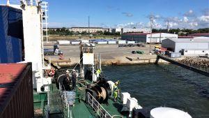 Ett fartyg anlöper hamn i Paldiski i Tallin. Sommar, blå himmel. Fotograferat från båten mot hamnen. Ganska tomt på folk, bilar och annat i hamnen.