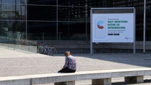 En kvinna sitter med sin mobiltelefon framför en reklam för den tyska corona-appen.