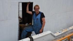 En man i blå overall står i en dörröppning på en vit metallbåt.