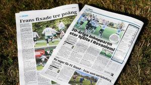 """Ålandstidningen och Nya Åland ligger på en gräsmatta. I tidningarna står det om Frans Grönlunds segermål för IFK Mariehamnn borta mot RoPS. """"Frans fixade tre poäng"""" och """"20-åriga inhopparen stor hjälte i Rovaniemi""""."""