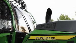 Närbild av en grön och gul John Deere skogstraktor.