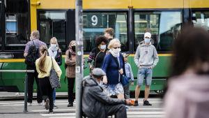 Människor vid en spårvagnshålltplats i Helsingfors. En del går över gatan. Många har munskydd på sig.