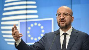 Charles Michel håller tal med handen utsträckt framför en blå bakgrund där EU:s flagga syns. Michel har runda glasögon, skägg och är skallig.