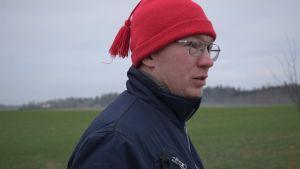 Jordbrukaren Erik Perklén med röd luva och grön åker i bakgrunden.