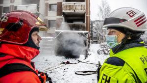 Två brandmän, en i röda skyddskläder och den andra i gula, och med skyddshjälmar pratar med varandra utanför ett höghus därifrån det bolmar ut svart rök.