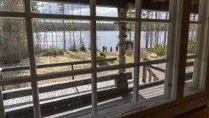 Utsikt över en sjö inne ifrån en sommarstuga.
