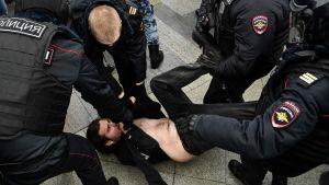 Poliser håller en man mot marken i Ryssland.