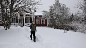 Trädgårdsmästare Lena Gillberg kommer gående längs en stig i snön framför Strömsövillan