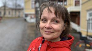 Kvinna i röd jacka står utomhus en regngrå dag, hon ler mot kameran.