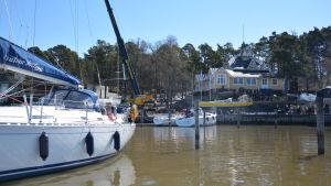 En segelbåt ligger förtöjd vid en brygga, i bakgrunden sjösätts en segelbåt med hjälp av en lyftkran.