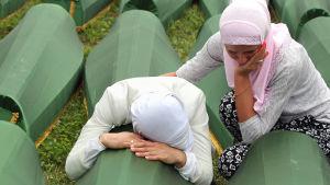 Bosniska muslimer sörjer över en kista i Potocari den 11 juli 2014. Under minnesceremonin begravdes 175 identifierade bosniakers kvarlevor.