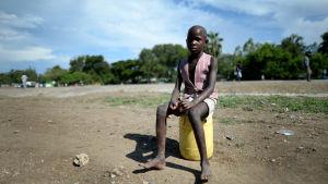En flicka sitter på sin vattenkanister vid Nyandofloden nära Kisumu i Kenya.