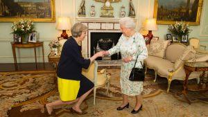 Theresa May knäböjer framför drottning Elizabeth II på Buckingham Palace.