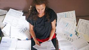 Kvinna sitter i ett hav av räkningar.
