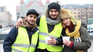 tre personer i vinterkläder med nationalteatern i Hfrs i bakgrunden