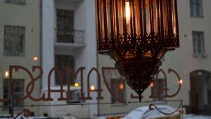 En lampa i Cafe Damascus med skyltfönstret i bakgrunden.