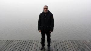 professor tommi lehtonen står på en brygga med ett dimmigt hav bakom sig. Han bär mörka kläder.